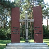 Далее за монументом между двумя стелами установлен памятный крест.